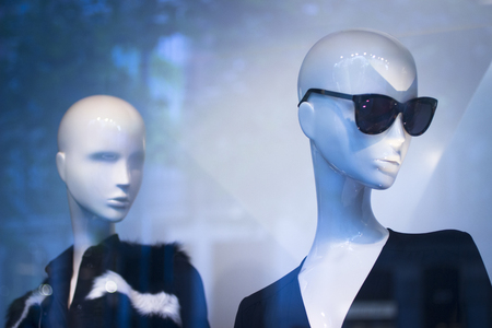 Shop dummy fashion mannequin in store boutique shop window wearing dark sunglasses artistic photo.