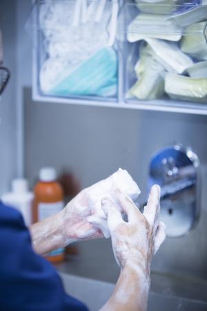 scrubbing: Traumatology orthopedic surgery hospital emergency operating room prepared for arthroscopy operation photo of nurse scrubbing doctor washing hands sterilising with sterilisation soap and products.