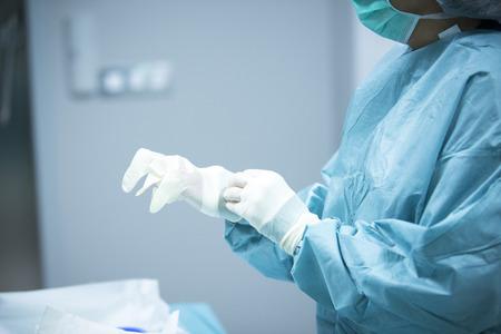外傷整形外科病院緊急手術室看護師が医師の手 insterile プラスチック手袋を入れをスクラブの関節鏡操作写真のために準備します。 写真素材 - 46408187