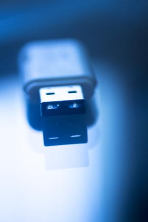 USB 3 flash drive III pendrive IT PC memory storage dongle plug socket close-up color artistic photo in blue tones. Stock Photo
