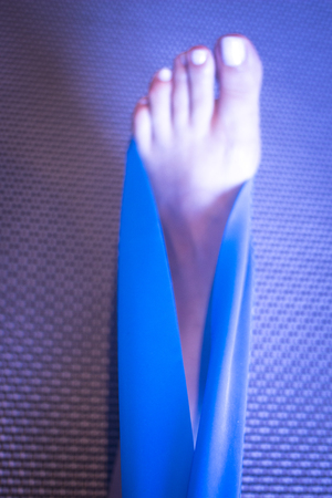 tendon: Pilates stretching leg hamstring foot achiles tendon yoga flexibility postural rubber band posture blue flexible strap health club held by young woman exercising.