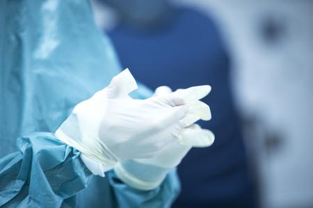 scrubbing: Traumatology orthopedic surgery hospital emergency operating room prepared for arthroscopy operation photo of nurse scrubbing doctor putting hands insterile plastic gloves. Stock Photo