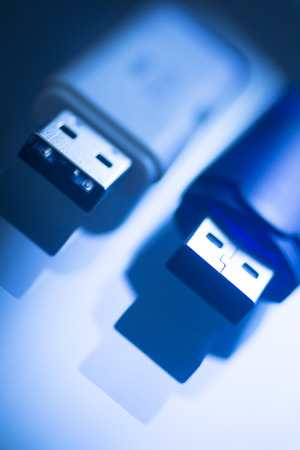 dongle: Two USB 3 flash drive III pendrive IT PC memory storage dongle plug socket close-up color artistic photo in blue tones. Stock Photo