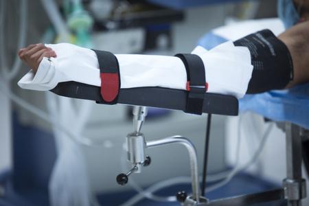 Traumatology orthopedic surgery hospital emergency operating room prepared for arthroscopy operation photo of immobilized arm. Stock Photo