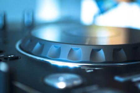 nightclub: DJ console cd mp4 deejay mixing desk Ibiza house techno dance music wedding reception party in nightclub with colored lighting effect disco lights.