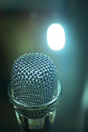 negative space: Professional studio voice recording concert singing microphone showing metallic body. Artistic color digital photo with shallow depth of focus and negative space and blurred background. Stock Photo