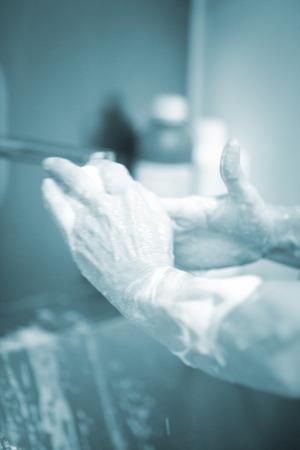 Traumatology orthopedic surgery hospital emergency operating room prepared for arthroscopy operation photo of nurse scrubbing doctor washing hands sterilising with sterilisation soap and products.