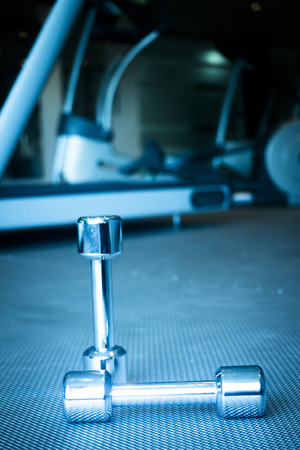 body conscious: Dumbbell gym metal weights in exercise room in sports bodybuilder gym health club fitness studio for bodybuilding and weight training. Stock Photo