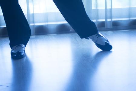Dancing shoes feet and legs of male ballroom and latin salsa dancer dance teacher in dance school rehearsal room class.