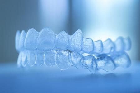 dientes: Invisible dental corchetes de los dientes alineadores dentales plástico tirantes retenedores para enderezar los dientes. Alisadores removibles temporales de ortodoncia en cirugía dental dentistas oficina foto en color clinic.Artistic en tonos azules creativas.