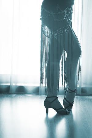Dancing shoes feet and legs of female ballroom and latin salsa dancer dance teacher in dance school rehearsal room class. Stock Photo
