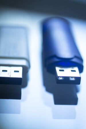 Two USB 3 flash drive III pendrive IT PC memory storage dongle plug socket close-up color artistic photo in blue tones. Stock Photo