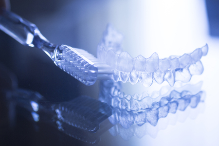 dental health: Invisible dental teeth brackets tooth aligners plastic braces retainers to straighten teeth and toothbrush dental hygien care. Orthodontic temporary removable straighteners in dental office dentists surgery clinic.Artistic color photo in creative blue ton Stock Photo