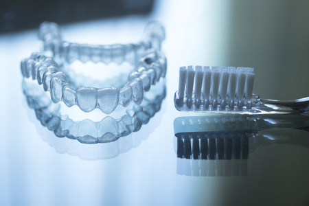 hygien: Invisible dental teeth brackets tooth aligners plastic braces retainers to straighten teeth and toothbrush dental hygien care. Orthodontic temporary removable straighteners in dental office dentists surgery clinic.Artistic color photo in creative blue ton Stock Photo