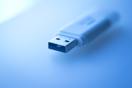 dongle: USB 3 flash drive III pendrive IT PC memory storage dongle plug socket close-up color artistic photo in blue tones. Stock Photo