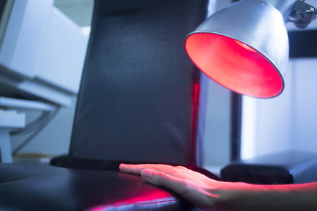 ligaments: Patient hand in red physiotherapy heat treatment under hot light. Stock Photo