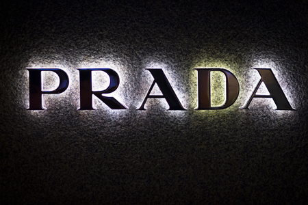 prada: Prada neon light logo shop fashion clothes store at night in high street. Editorial