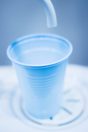 pip: Dentists water rinse cup tap pip filler in dental clinic in artistic blue purple white tones. Stock Photo