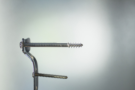 implantology: Traumatology and orthopedic surgery implant titanium plate and screws in semi silhouette against plain studio background. Stock Photo