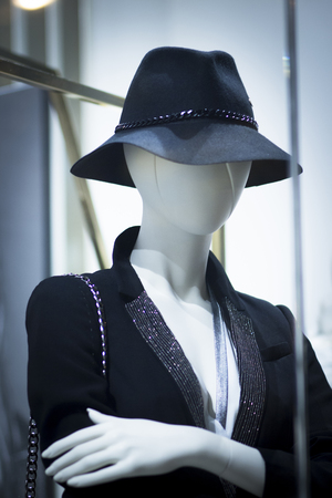 garments: Shop dummy fashion mannequin in department store boutique window wearing current trends in garments. Stock Photo