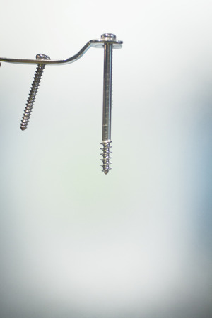 titanium: Traumatology and orthopedic surgery implant titanium plate and screws in semi silhouette against plain studio background. Stock Photo