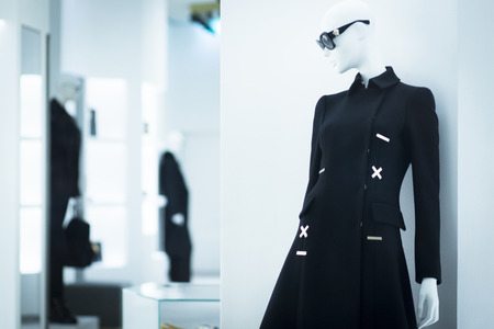 Shop dummy fashion mannequin in department store boutique window wearing current trends in garments. Banco de Imagens
