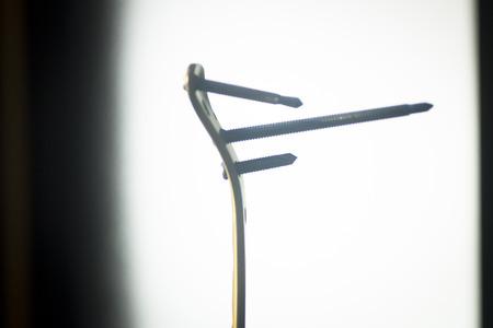 traumatology: Traumatology and orthopedic surgery implant titanium plate and screws in semi silhouette against plain studio background. Stock Photo