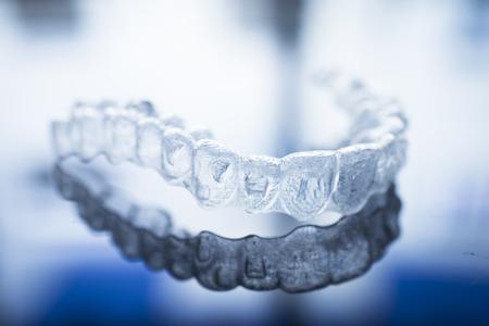 odontologa: Invisible corchetes de los dientes dentales alineadores de dientes de plástico se prepara retenedores de odontología para enderezar los dientes. Ortodoncia removibles alisadores temporales en la oficina del dentista clínica de cirugía dental. Foto de archivo