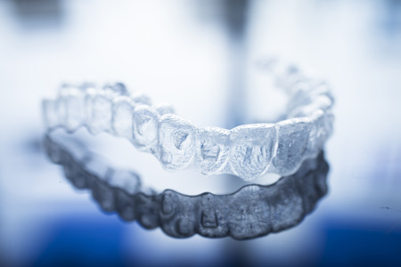 Invisible dental teeth brackets tooth aligners plastic braces dentistry retainers to straighten teeth. Orthodontic temporary removable straighteners in dentist office dental surgery clinic.