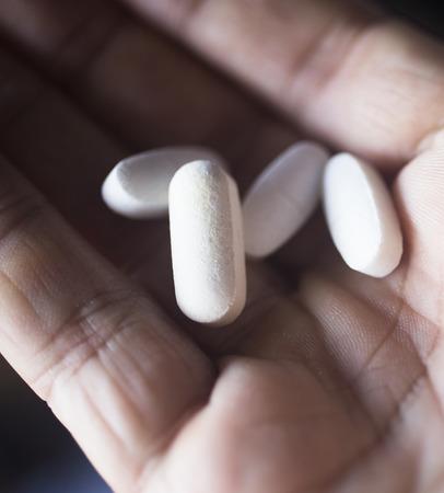 pain killer: Multivitamin mineral pills health food supplements in hand of man.