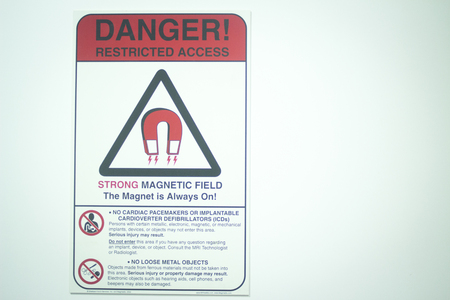 magnetismo: Fully open high field Magnetic Resonance Image MRI Nuclear CAT Scan scanner nuclear magnetism warning sign outside room on door. Archivio Fotografico
