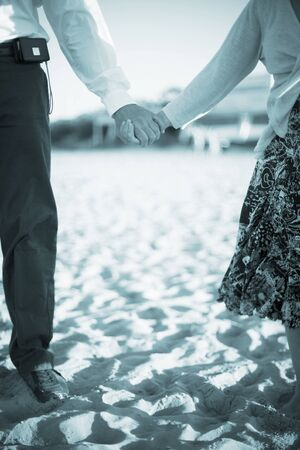 newly weds: Wedding bride and bridegroom in suit in beach marriage ceremony holding hands in romantic photo.