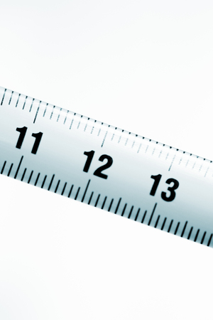 12 13: Measuring tape metal ruler showing measuement in centimeters 11 12 13 (cm) numbers on plain background.