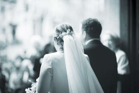 newly weds: Wedding bride in white dress and bridegroom in suit in marriage exiting church. Stock Photo