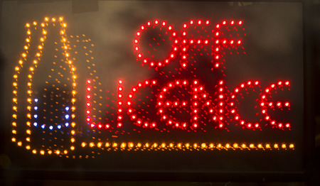 Off licence liquor store alcohol for sale neon light sign at night photo. Stock Photo