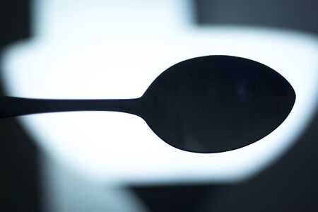 symbolic: Spoon silhouette at night symbolic artistic photograph.