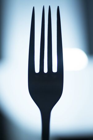 symbolic: Fork silhouette at night symbolic artistic photograph.