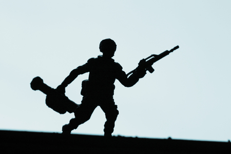 paramilitary: Toy military soldier and gun silhouette photo.