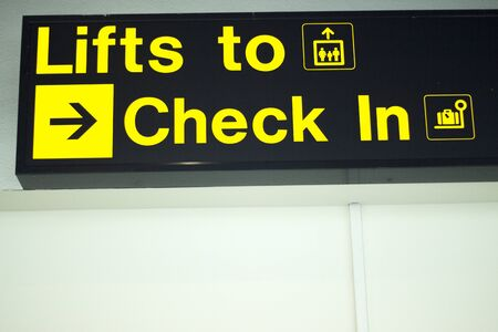 checkin: Airport information sign light panel giving directions for checkin for air travelllers.