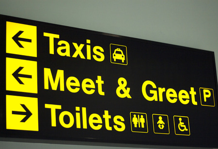 meet and greet: Airport information sign light panel giving directions in arrivals lounge for taxi, meet and greet and toilets. Stock Photo
