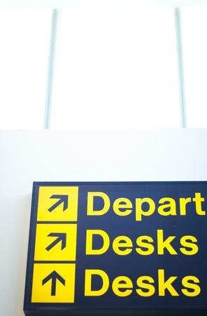 departures: Airport departures and desks sign information sign light panel giving directions.