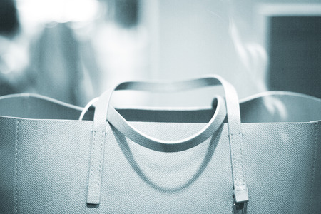 designer bag: Shop window luxury fashion clothes store designer leather handbag photograph.