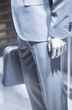 leather briefcase: Store mannequin in gray business suit carrying luxury leather briefcase photo. Stock Photo