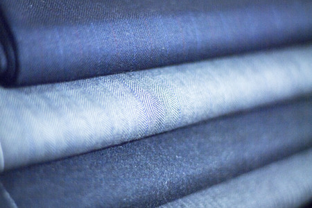 Lambs wool suit  cloth for meade to measure shirts in tailors retail store window photo.