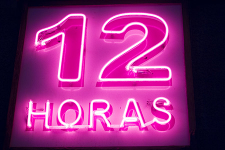 12 hour: Pharmacy neon light chemists 12 hour open pink sign at night photo. Stock Photo