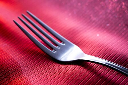 special steel: Stainless steel fork on dinner table place setting in restaurant wedding party photo. Stock Photo