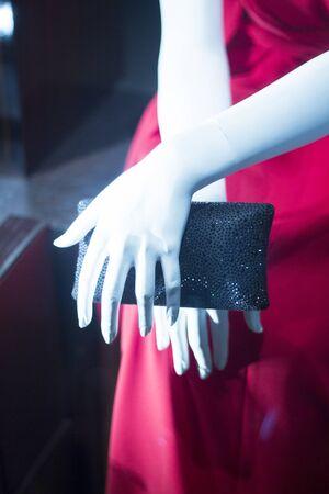 clutch bag: Department store mannequin carrying leather luxury clutch bag handbag in shop window.