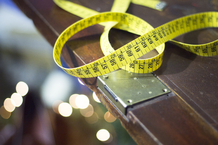 made to measure: Tape measure in tailors store hand made suits and shirts menswear window.