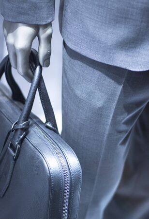 leather briefcase: Store mannequin carrying luxury leather briefcase photo. Stock Photo