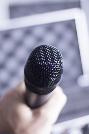 held: Audio recording vocal studio professional microphone to record singing or voice-overs held in hand of man.